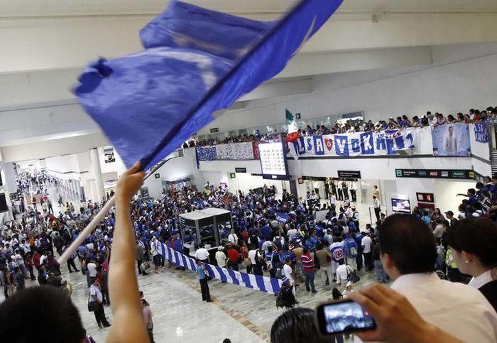 Fueron cientos los aficionados del Cruz Azul que colmaron la Terminal 1 del aeropuerto de la Ciudad de México. (Notimex)