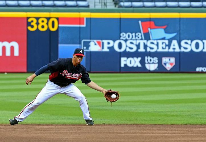 El shortstop de Atlanta, Andrelton Simmons, cacha una bola durante el entrenamiento de este miércoles. (Agencias)