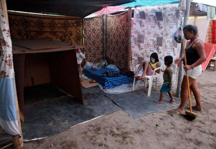 Una familia adecúa un refugio temporal tras el terremoto del sábado pasado, en Manta, Ecuador. (EFE)