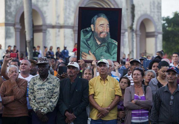 Cubanos esperan el paso de la urna con las cenizas del fallecido líder de la revolución cubana Fidel Castro en la ciudad de Camagüey. (EFE)