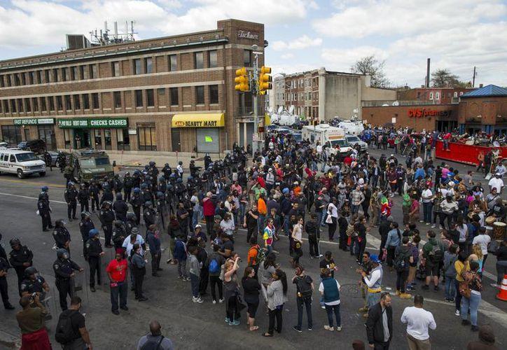 Un grupo de manifestantes protesta frente a policías tras el funeral del afroestadounidense Freddie Gray en Baltimore, quien falleció de lesiones vertebrales después de ser arrestado y trasladado en una camioneta del Departamento de Policía de Baltimore. (Foto AP/Patrick Semansky)