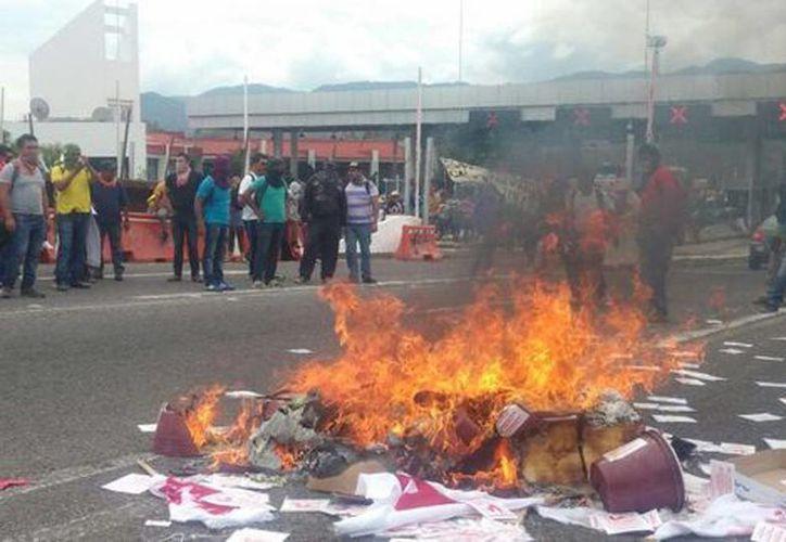 Los manifestantes quemaron propaganda del Partido de los Pobres de Guerrero y cubetas en la caseta de Palo Blanco, en la Autopista del Sol, en Guerrero. (Rogelio Agustín)