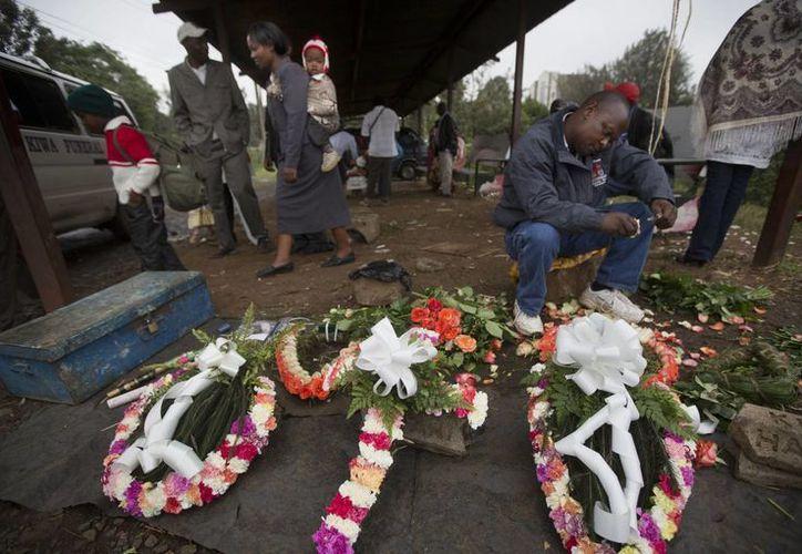 Floristas elaboran ofrendas florales afuera de un cementerio, para ofrecerlas  en honor a las víctimas abatidas en el centro comercial de Nairobi, Kenia. (Agencias)