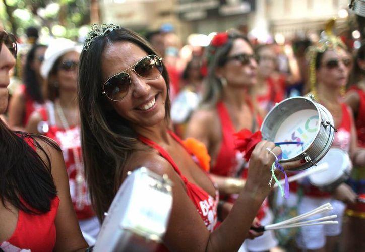 """Una mujer sonríe en el barrio de Botafogo, en Río de Janeiro. Los bloques callejeros de comparsas, como el de este domingo realizado por el grupo """"Só Caminha"""" (Sólo camina) en el tradicional barrio de Botafogo y bajo un inclemente sol, """"calientan"""" literalmente en Río de Janeiro el carnaval que se celebrará en todo el país entre el 13 y 18 de febrero próximos. (EFE)"""