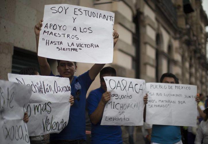 Unos estudiantes protestan durante una manifestación en la ciudad mexicana de Morelia en contra de los enfrentamientos entre integrantes de la CNTE y agentes policiales en el estado de Oaxaca, el pasado domingo. (EFE)