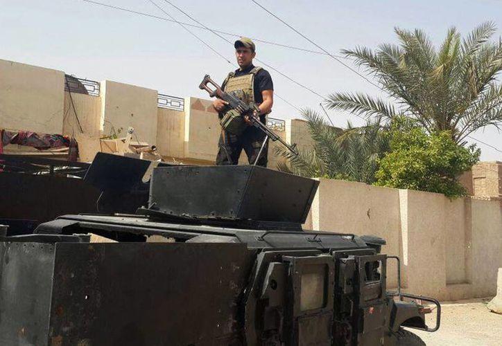 Un soldado monta guardia encima de su vehículo blindado en el barrio Estadio Sur de Ramadi, Irak. (Agencias)