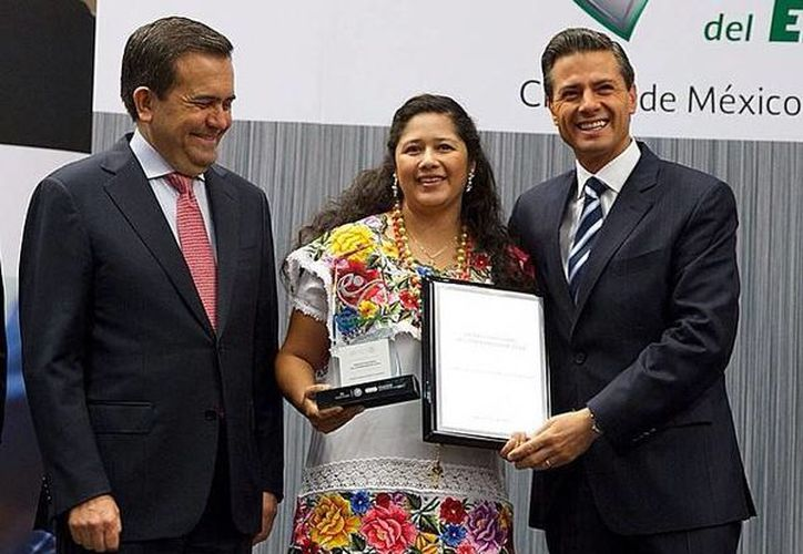 El presidente Enrique Peña Nieto entrega el Premio Nacional del Emprendedor a la yucateca Maritza Aurora Morales Casanova. Los acompaña el director del Inadem, Enrique Jacob Rocha. (Presidencia de la República)