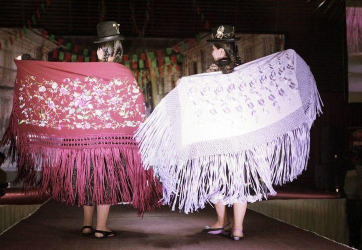 """Jóvenes bolivianas lucen las últimas tendencias en moda tradicional. """"Cholita"""" es el apelativo cariñoso con el que se conoce en Bolivia a la mujer indígena aimara ataviada con bombín, pollera, blusa, manta y con el largo cabello recogido en dos trenzas que caen a su espalda. (EFE/Archivo)"""
