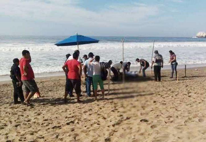 Este sábado un hombre murió ahogado en la playa de San Agustín, de las Bahías de Huatulco. Imagen de los socorristas de la Cruz Roja Mexicana al darle reanimación cardiopulmonar, pero sin éxito. (Excelsior)