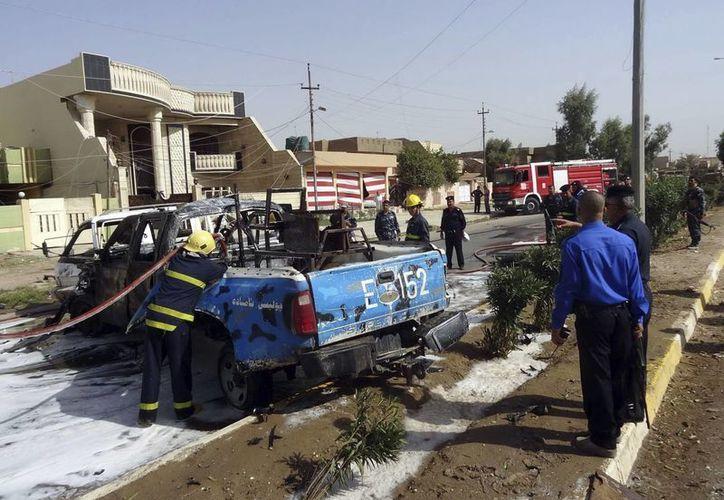 Agentes de policía y bomberos inspeccionan un coche de policía en el lugar donde un coche bomba fue detonado en la ciudad de Kirkuk, Irak. (EFE)
