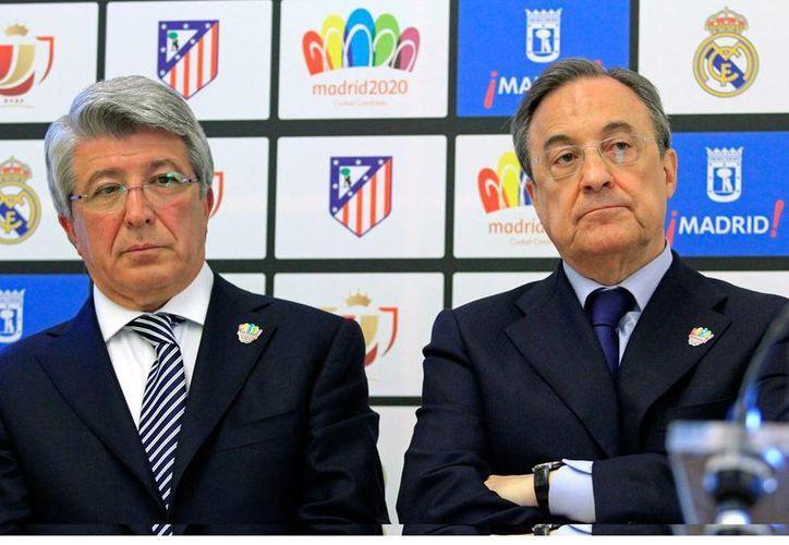 Los clubes Atlético de Madrid y Real Madrid no podrán fichar a ningún jugador en los próximos 'mercados de piernas': FIFA los sancionó por violar el reglamento de traspasos de menores de edad. En la imagen, Enrique Cerezo (izq.) Florentino Pérez, presidentes de los clubes. (Efe/Archivo)