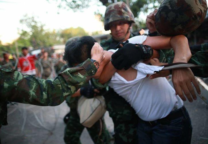 Un manifestante es detenido por soldados tailandeses durante una manifestación contra el golpe de estado. (Agencias)