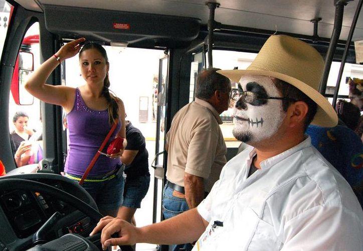 De acuerdo con el Gobierno, el número de turistas que arribó a la entidad en 2013 (1'117,000) es mayor al de 2012. En la imagen, el chofer -maquillado como ánima en pena del Hanal Pixán- de un autobús turístico recibe a turistas nacionales. (Archivo/Milenio Novedades)