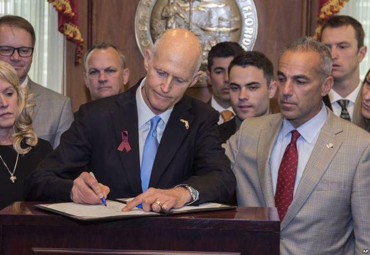 El gobernador de Florida, Rick Scott, firma la Ley de Seguridad Pública que impone mayores controles a las ventas de armas. (Foto: AP)