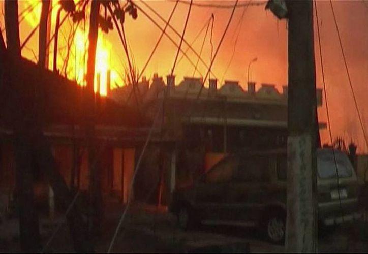 Imagen tomada de video en las que se aprecian flamas detrás de casas después del estallido. (Agencias)