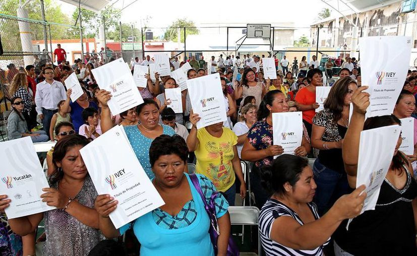 Beneficiarios del fraccionamiento Cideco de Conkal muestran los títulos que avalan la propiedad de sus viviendas. (Cortesía)