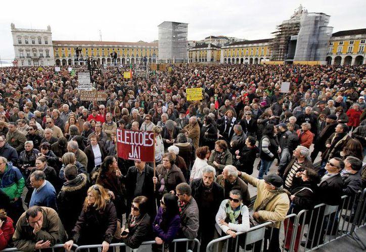 Manifestantes portugueses con pancartas gritan para pedir el final de las políticas de austeridad. (EFE)