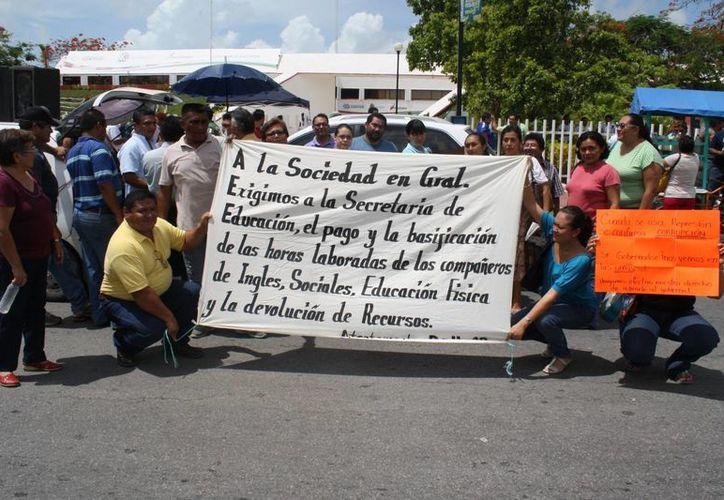 Aspectos de la manifestación de maestros realizada ayer por la mañana en las instalaciones de la SEQ. (Harold Alcocer/SIPSE)