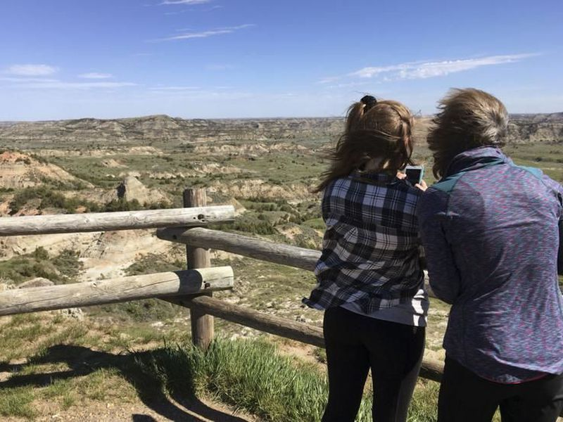 Jeanne Randall, right, and her daughter Zoe, of Shoreview, Minn., take photos at Painted Canyon in Theodore Roosevelt National Park in western North Dakota.