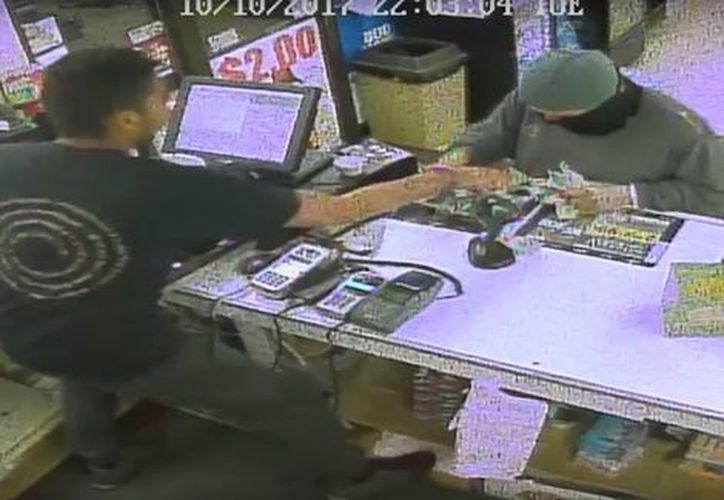 En un video de vigilancia, publicado en YouTube, se observa al sujeto que apuntaba con una pistola al cajero y le pedía el dinero. (Milenio)