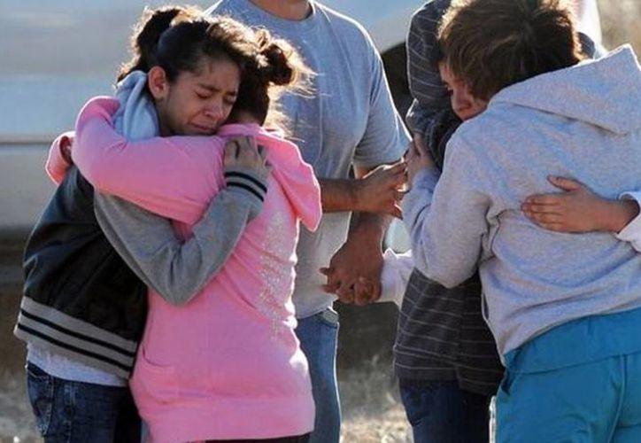 Familiares reciben a sus hijos al salir del lugar del tiroteo en Nuevo México. (Agencias)