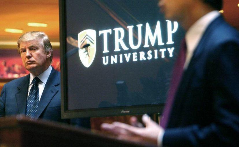 stra a Donald Trump (izq), presentado por Michael Sexton en una rueda de prensa en Nueva York donde él anunció el establecimiento de la Universidad Trump, que hoy se encuentra en medio del escándalo. (Archivo/AP)