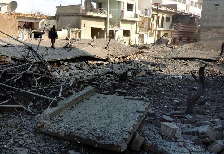 Un rebelde sirio observa los daños tras un ataque en  Bensh al norte de Siria. (Archivo/Agencias)