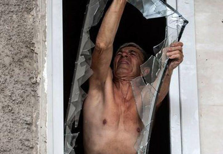 Un ciudadano quita una ventana dañada a causa de los enfrentamientos entre rebeldes en un edificio, en Donetsk, lugar en el que fallecieron -en un hecho diferente al de la imagen- 4 personas por enfrentamientos entre rebeldes prorrusos y el Gobierno. (AP)
