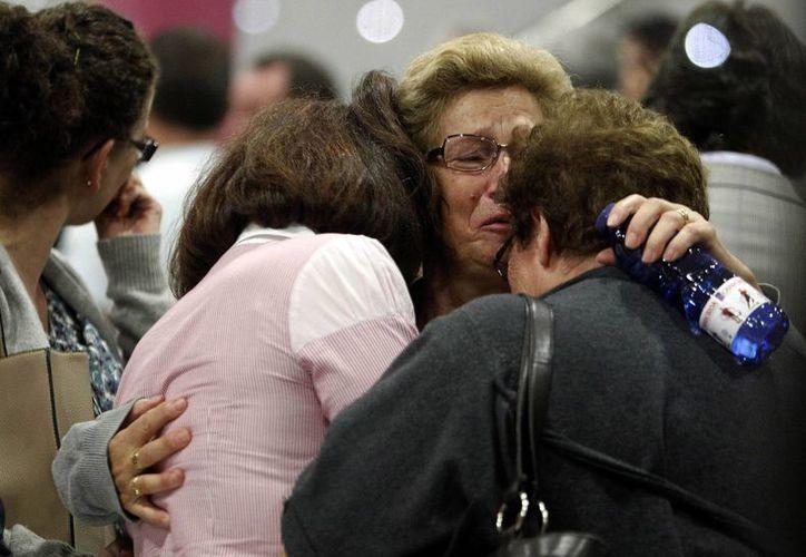 Los familiares de las víctimas del accidente ferroviario lloraban y se abrazaban. (Agencias)