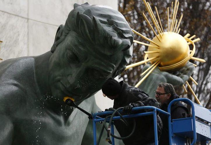 Dos operarios limpian la estatua 'El espíritu de Detroit' eregida en 1955 y obra de Marshall Fredericks, frente al centro municipal de Juventud Coleman en Detroit. (EFE)