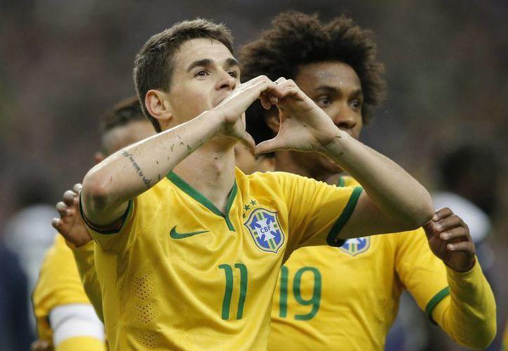 El brasileño Oscar celebra con su compañero Willian, tras anotar en un partido amistoso contra Francia. (AP)