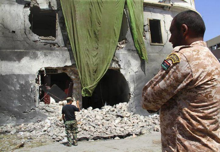 Soldados libios observan el edificio perteneciente al Ministerio de Asuntos Exteriores destruido en una fuerte explosión, en el centro de Bengasi. (Archivo/EFE)