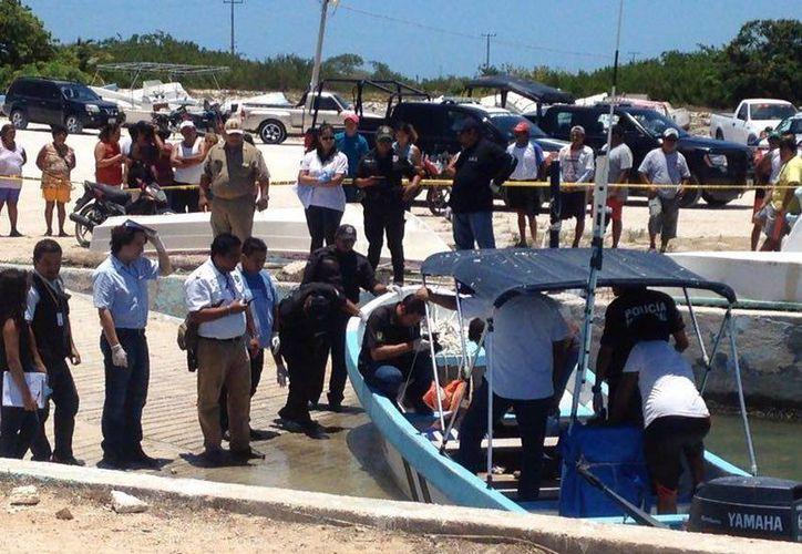 Imagen del momento en que autoridades realizan las primeras investigaciones de la muerte del pescador. (Gerardo Keb/Milenio Novedades)