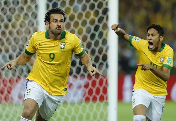 Fred (i) y Neymar celebran el gol del primero que abrió el marcador y puso en ventaja a Brasil. (Agencias)
