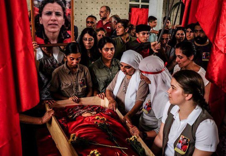 Dolientes reunidos en torno al cuerpo de Gulay Ozarlan, una miliciana del grupo DHKP-C, muerta en un tiroteo con la policía durante una gran operación contra el grupo ilegalizado, en Estambul, Turquía. (AP Foto/Cagdas Erdogan)