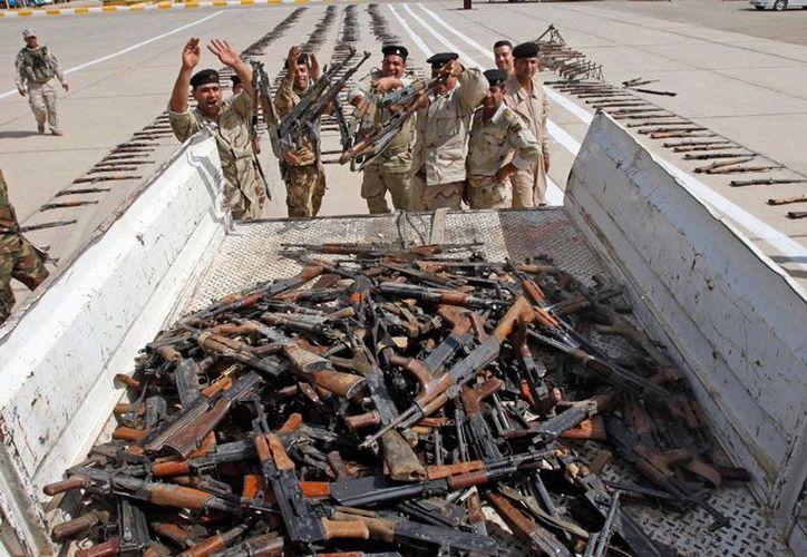 Soldados del ejército iraquí cargan un camión que transporta armas incautadas por las fuerzas de seguridad iraquíes. (Archivo AP)