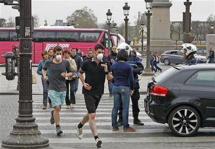 Dos corredores se protegen con máscaras de la contaminación en París, el lunes 17 de marzo de 2014. El lunes los vehículos con placas terminadas en par no pudieron circular en la capital de Francia debido a los altos niveles de contaminación. (Foto AP/Remy de la Mauviniere)