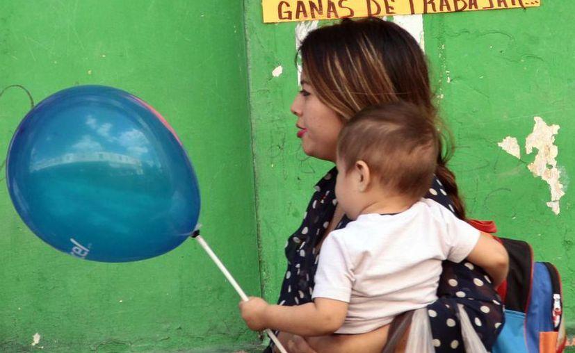 Especialista recomienda que los recién nacidos o lactantes no deberá ser expuestos  a una fórmula láctea. Imagen de contexto de una mujer con su hijo caminando en una calle de Mérida. (Milenio Novedades)