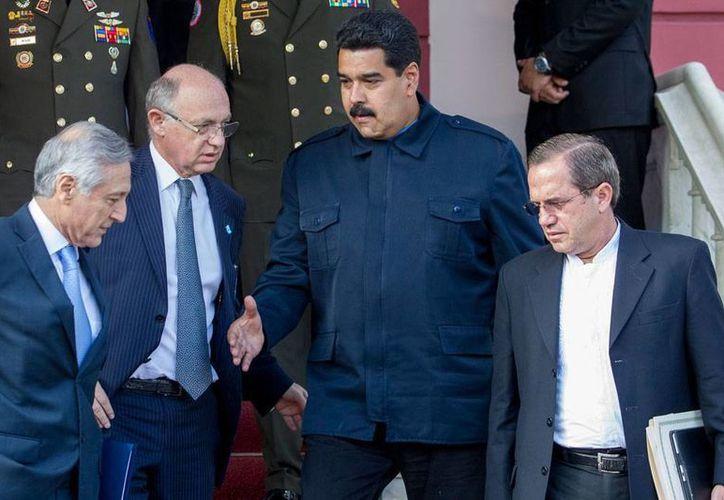 Nicolás Maduro acepta la propuesta de Unasur de reunirse mañana con la oposición. En la imagen, el Presidente de Venezuela (bigote), se despide del canciller argentino, Héctor Timerman (i), y del ecuatoriano, Ricardo Patiño (izq.), tras sostener una reunión con los demás cancilleres de la Unión de Naciones Suramericanas (Unasur). (EFE)