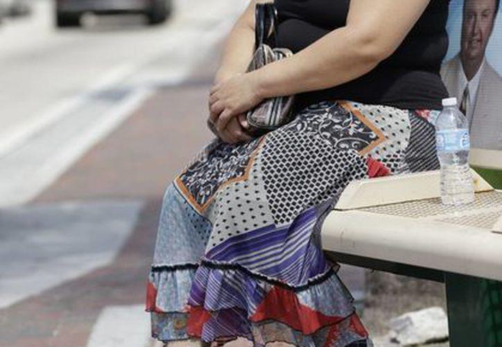 La hondureña Diana Hernández aguarda en una parada de autobús al otro lado de la calle donde se encuentran unas oficinas de inmigración en North Miami, Florida. (Agencias)