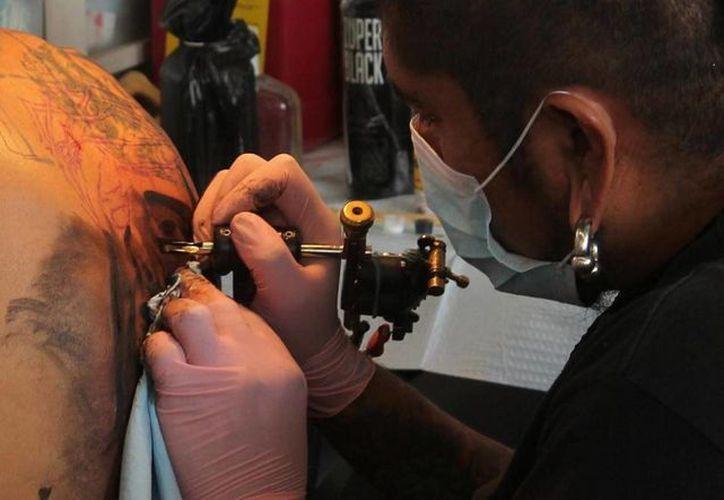 El PRI propone castigos de hasta tres años de prisión a quien discrimine a personas con tatuajes o perforaciones. (Archivo/Notimex)