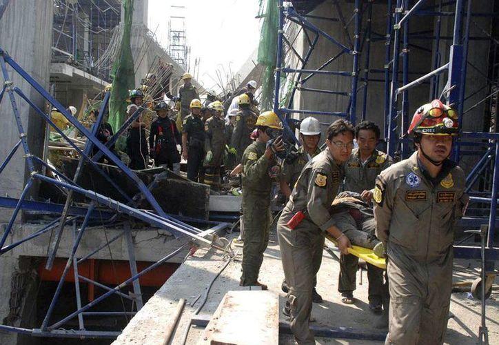 Trabajadores de servicios de emergencia trasladan a un herido tras el derrumbe de un edificio en construcción en Samut Prakan, a las afueras de Bangkok. (EFE)