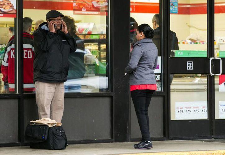 Los investigadores trabajan la escena del crimen en una tienda de conveniencia 7-Eleven en la zona de Boulevard Park de South King County, Washington. Al parecer, un cliente mató a un hombre que lo amenazó con un hacha para asaltar. (Bettina Hansen / AP)
