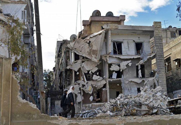 Unos civiles pasan por un edificio destruído por un ataque aéreo por parte del régimen sirio en el barrio de Kalase en Alepo, Siria. (Archivo/EFE)