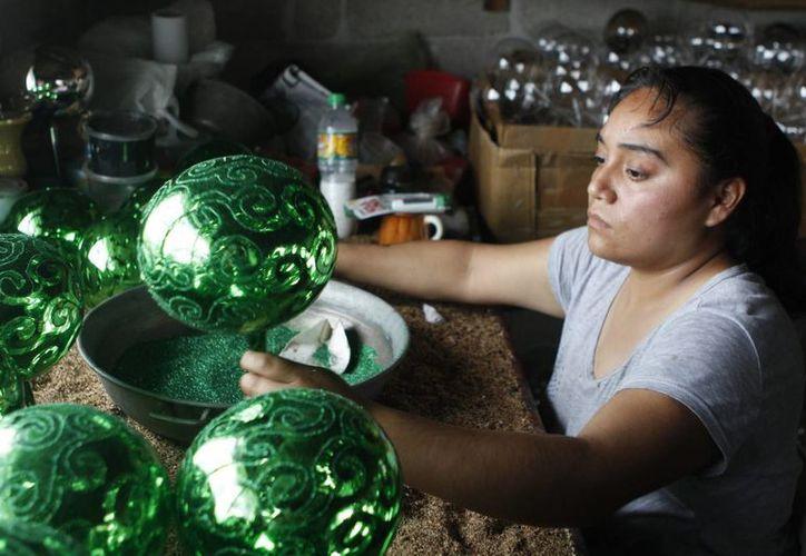 Las esferas del municipio de Chignahuapan son conocidos a nivel mundial debido a la amplia gama de diseños, formas y colores que realizan sus creadores. Imagen de una artesana del lugar. (Archivo/Notimex)