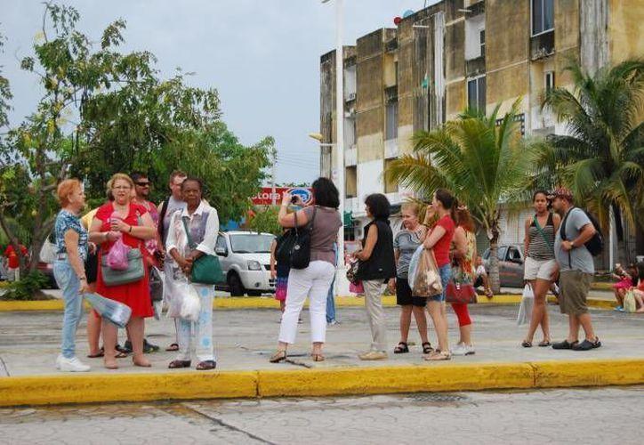 Los turistas reciben asesoría de los jóvenes para que sepan qué lugares de la entidad son de interés. (SIPSE/Archivo)