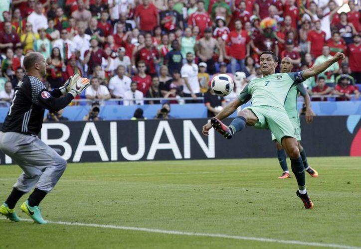 El portugués Cristiano Ronaldo reta al portero húngaro Gabor Kiraly (izquierda), durante el partido de fútbol del Grupo F de la Euro 2016, entre Hungría y Portugal, en el Grand Stade en Decines-Charpieu, cerca de Lyon, Francia. (Foto AP/Pavel Golovkin)