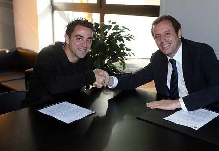 Xavi Hernández con el presidente del club, Sandro Rosell. (fcbarcelona.com)