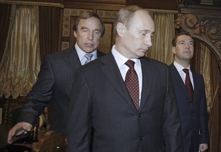 El violoncelista ruso Sergei Roldugin, izq., escolta al entonces primer ministro Vladimir Putin, centro, y el entonces presidente Dmitry Medvedev tras una gira a la Casa de la Música en San Petersburgo. (Agencias)