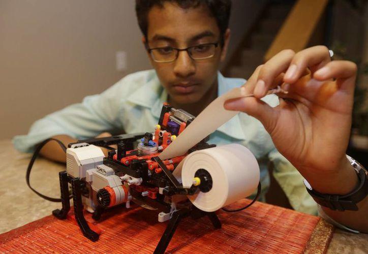 Shubham Banerjee trabaja en su modelo robótico de impresora braille en su hogar el 6 de enero del 2015 en Santa Clara, California. (Agencias)